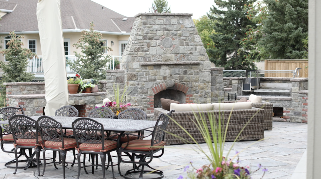 Outdoor Fireplace with Argentinian grill in new landscaped Calgary yard